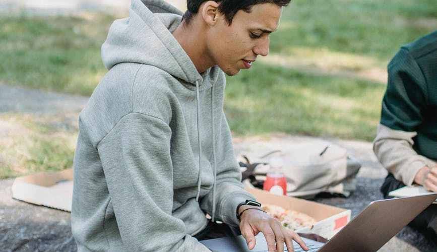 serious student surfing laptop during studies with classmate