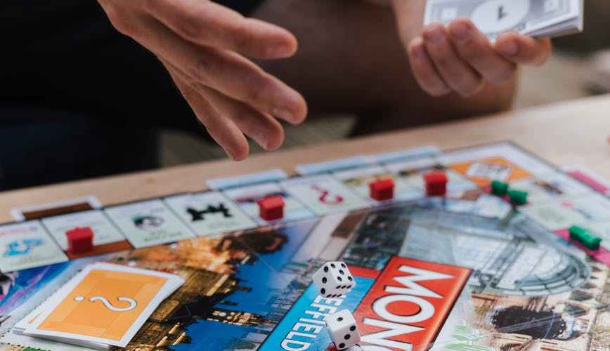 crop male player with game money playing monopoly