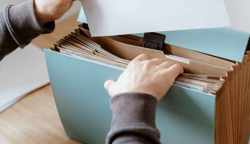 man opening blue briefcase with documents