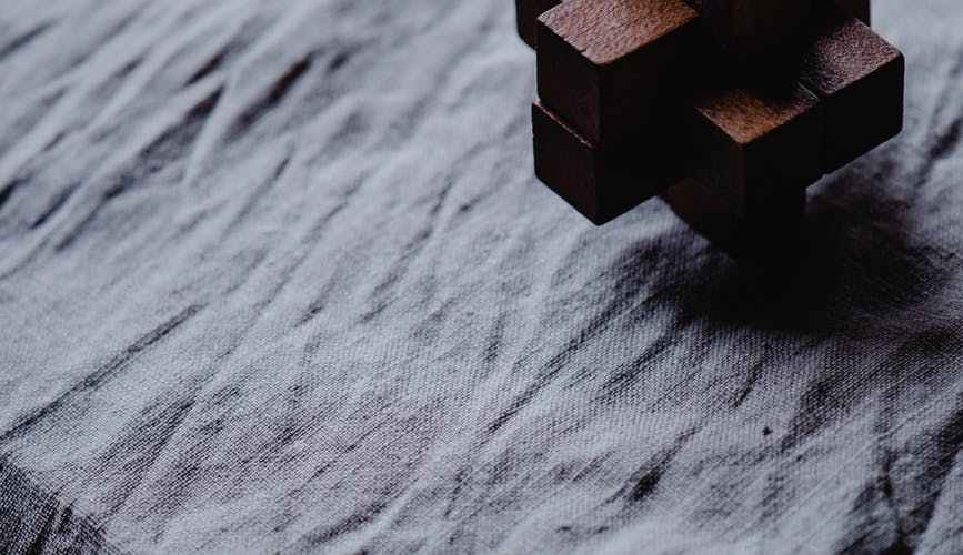 brown wooden cube on gray textile