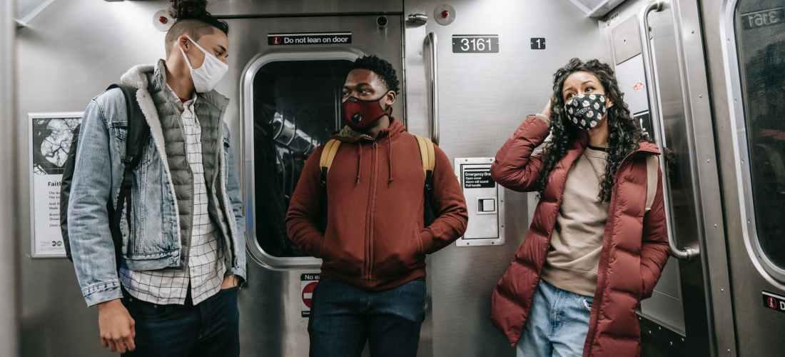 unrecognizable multiethnic friends in masks standing in subway train